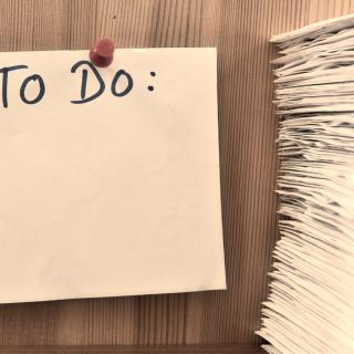A blank to do list on the wall next to a large stack of papers