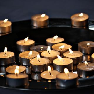 Small tea light candles lit and collected on a tray
