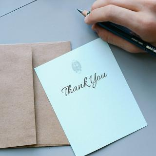 Hand with pen next to a thank you card