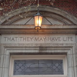 "An inscription on the stone lintel over a doorway: ""THAT THEY MAY HAVE LIFE."""