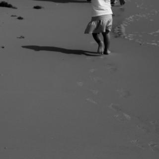 From the arms down, a toddler leaves footprints on the beach, her back to the camera.