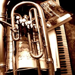 a tuba, piano, and sheet music in a sepia tones