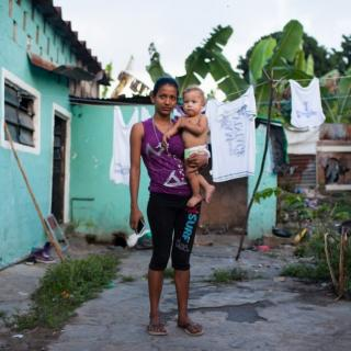 Honduran woman holding her one-year-old son next to a teal house with clothesline outside.