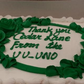 "A cake inscribed with ""Thank you Cedar Lane from the UU-UNO"""