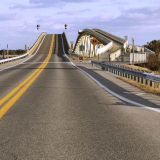 A two lane highway rises on to a steep bridge.