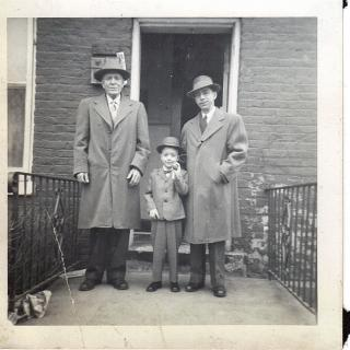 A square, faded, black-and-white photograph showing two men in overcoats, and a small boy in a suit, giving the impression of three generations.