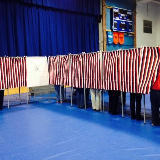 Inside of a school gymnasium, red-white-&-blue curtains hang along a string of voting booths, with some voters visible.