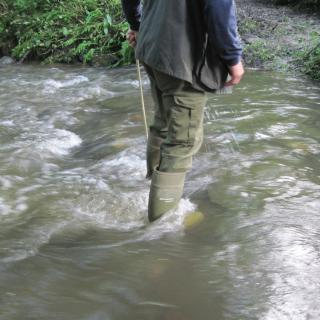 An adult in rubber boots walks through swirling water.