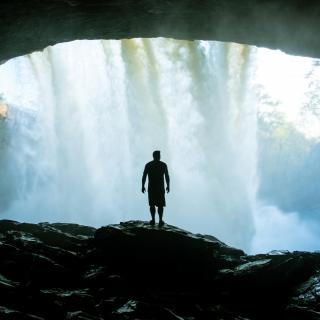 A person, in silhouette, stands under the sheltered lip of a strong waterfall