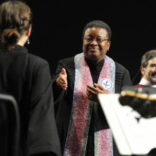 Rev. Natalie Fenimore extends a hand to welcome a new UU minister to fellowship at the 2013 Service of Living Tradition.