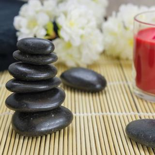 Stack of rocks and a candle on a bamboo mat