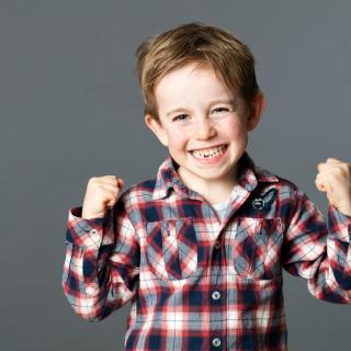 White boy about eight years old showing confident excitement and wearing a plaid shirt