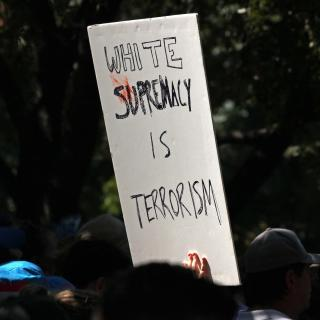 "Over the heads of people at a protest, a sign on white posterboard in black marker: ""White supremacy is terrorism."""