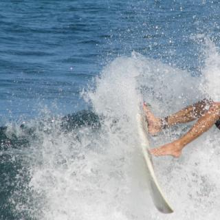As an ocean wave splashes, a surfboard and a pair of legs are shown mid-wipeout.