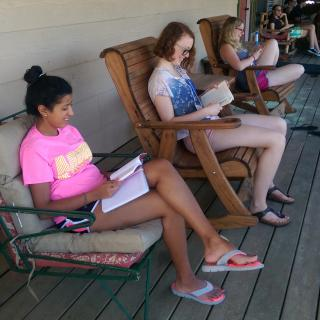 three young adults sit in chairs reading books on a porch