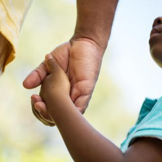 An adult hand holding a child's hand, the face of the child, a black boy, is partly visible.