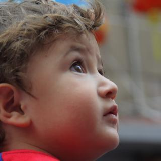 a child's face is shown in close-up profile as the child looks upward, wonderingly