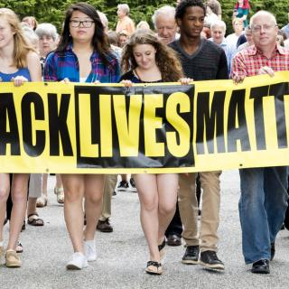 UU Annapolis Youth lead a marching crowd carrying Black Lives Matter Banner