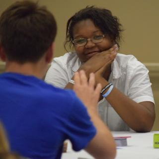 a young black woman wearing glasses looks encouragingly at a person who is facing her, speaking. that person is blurry and not the focus of the picture.