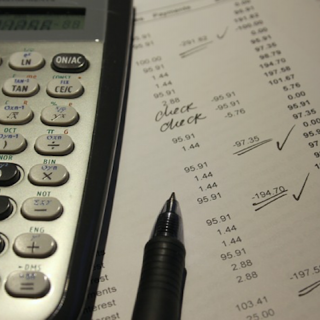 Calculator on top of financial reconciliation sheet with pen