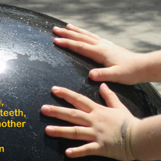 "A black marble globe with the hands of a white child pushing on it, superimposed with a quotation ""You get up in the morning, you brush your teeth, and you help another human being."""
