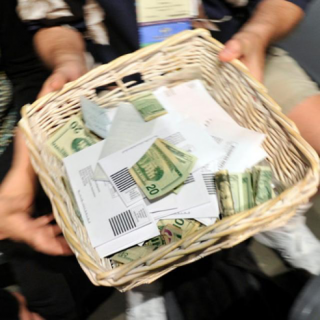 Hands passing a basket with cash and envelopes