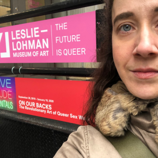 Jade, a white nonbinary person, in front of the Leslie-Lohman Museum of Art with an poster for On Our Backs, and exhibit about Queer Sex Work