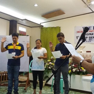 Four people stand holding up right hand to take oath, at UU Church of the Philippines