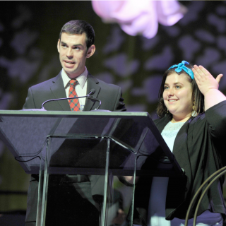 a young man speaks into a microphone, two young adults stand at a podium onstage, a young woman speaks into a microphone