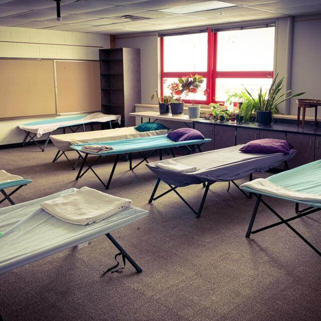 Clean sheets in shades of purple, white, and light blue stretch appealingly over rows of cots at Shawnee Mission Unitarian Universalist Church, ready for those without shelter.