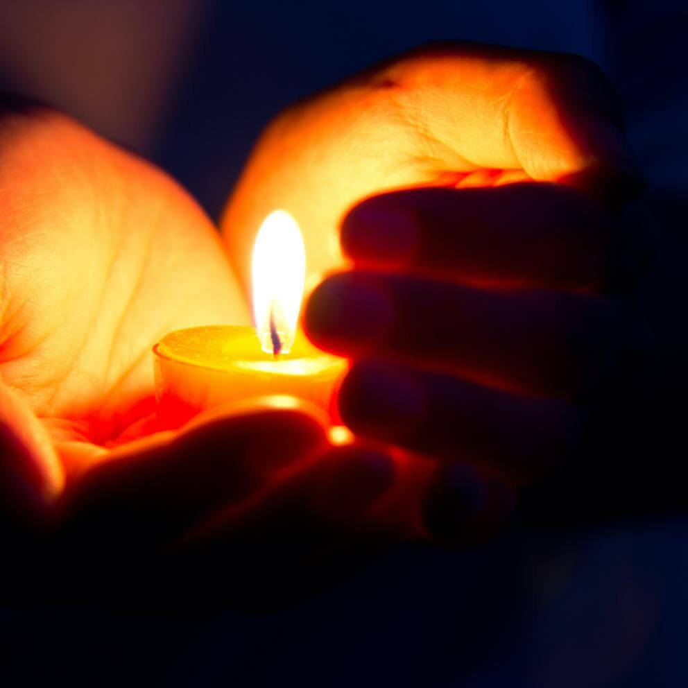hands holding a lighted candle