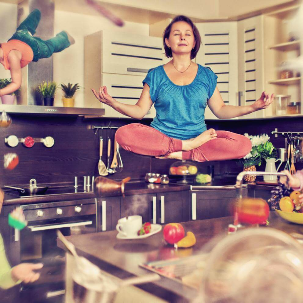 photo illustration of meditating woman in kitchen surrounded by children and swirling objects in mid-air