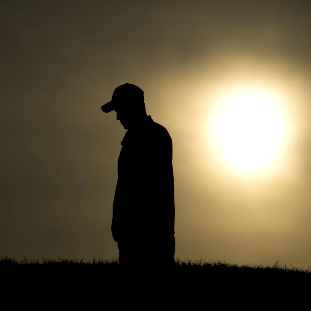 Silhouette of man looking down with sunset in background.