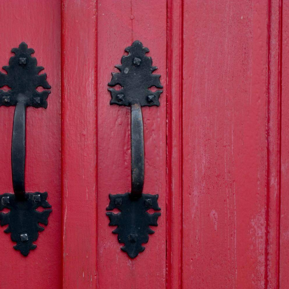 Two handles on a red church door.