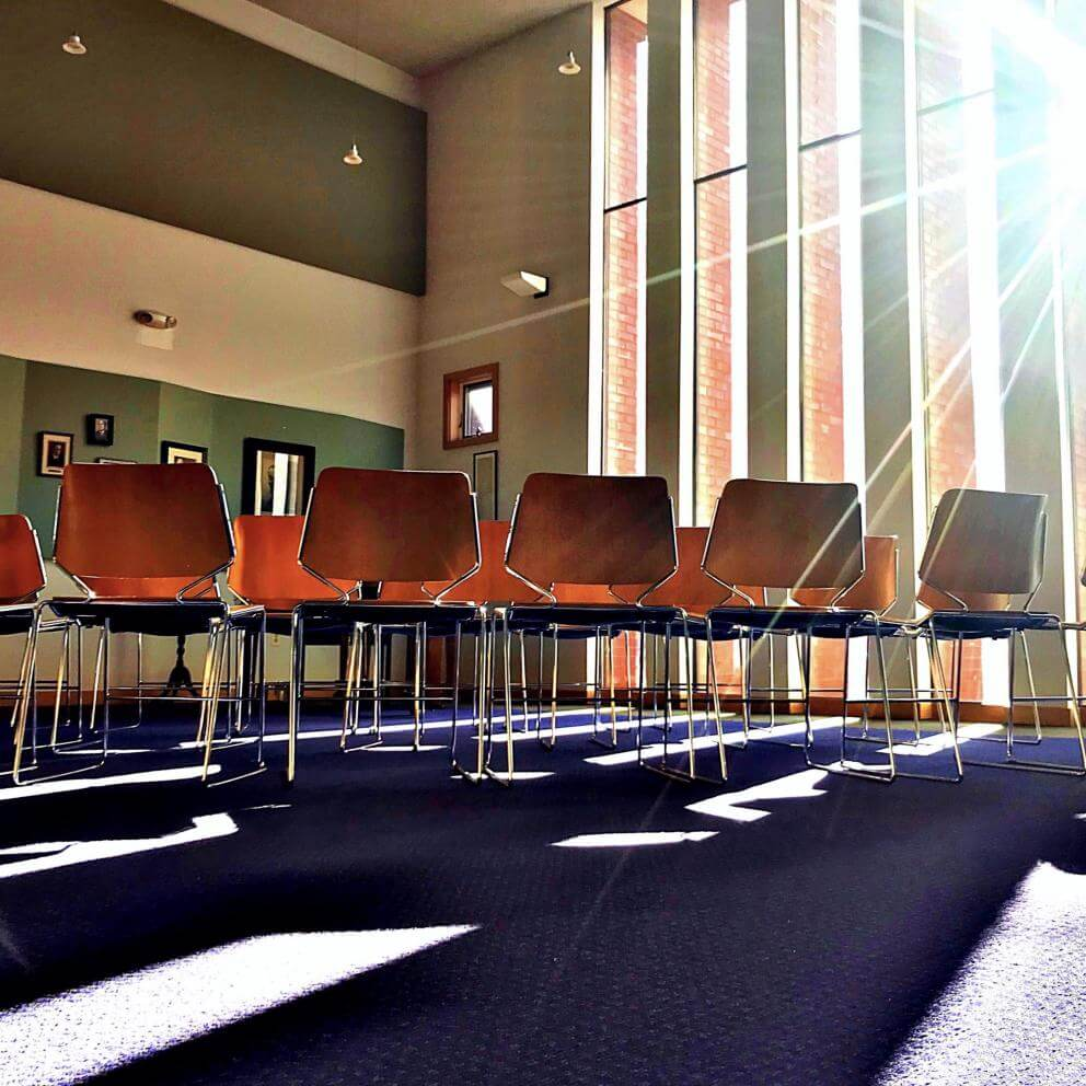 Photograph entitled First UU Congregation of Ann Arbor, Michigan (December 2018). A room with chairs and sunlight streaming in.