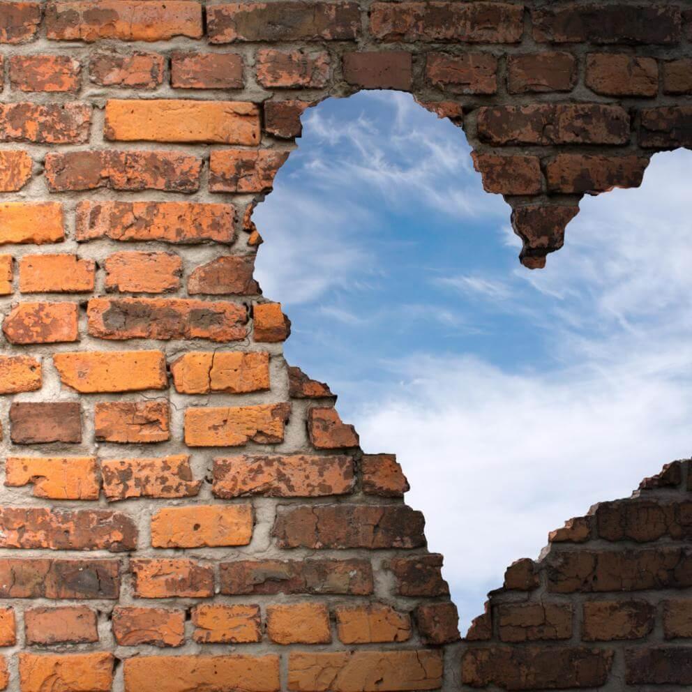 Photo illustration of old brickwork with a hole in the form of a heart, showing blue sky.