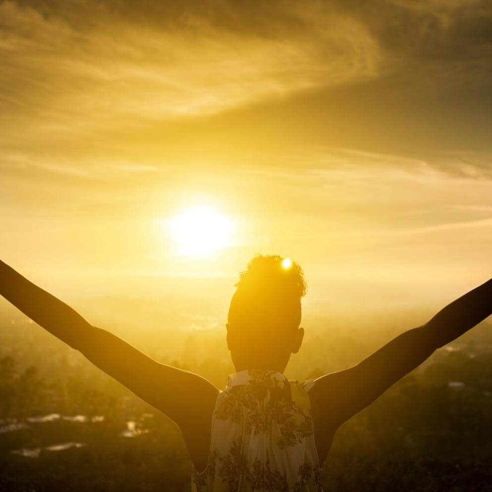 Black Girl Raising Arms over Valley in Sunset stock photo
