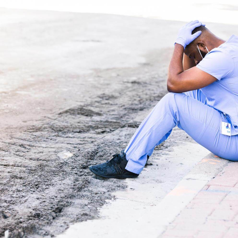 Distraught nurse takes break during COVID shift stock photo