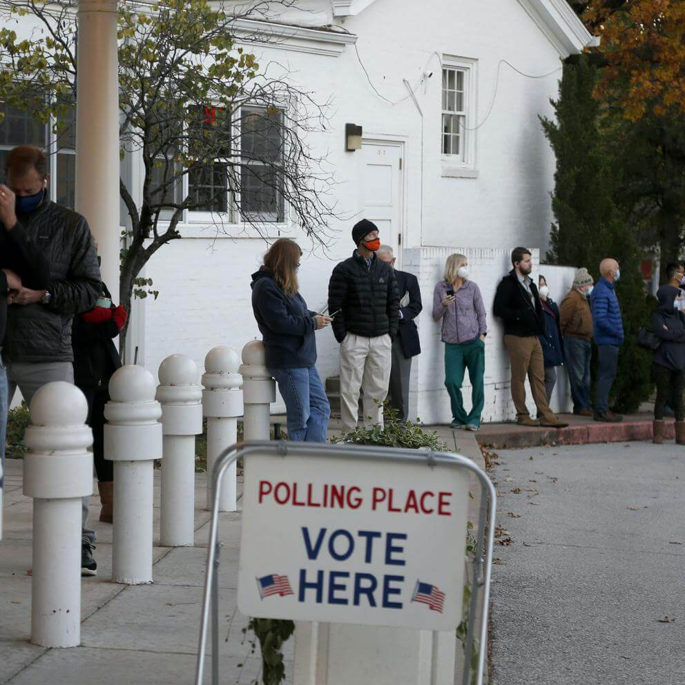 Voters wait in line before the polls open at All Souls Unitarian Church in Tulsa, Okla., Tuesday, Nov. 3, 2020