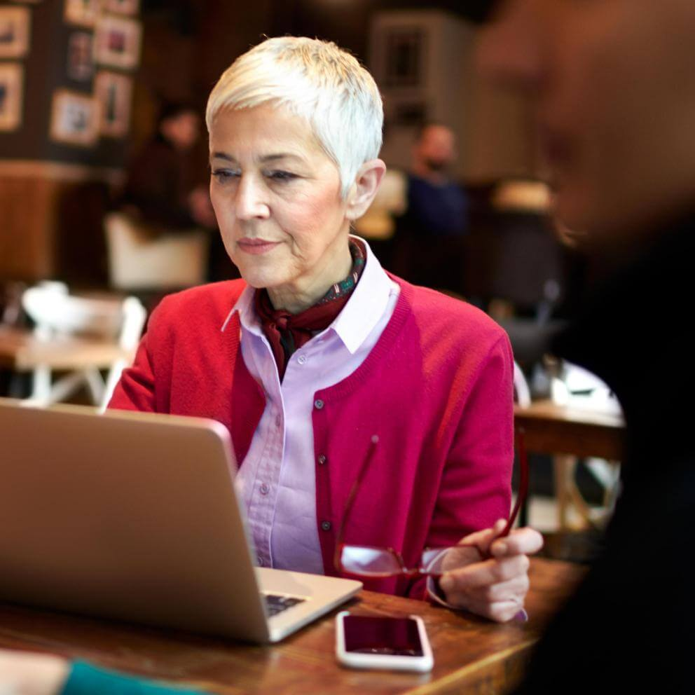 Mature woman working on a laptop at a coffee shop.
