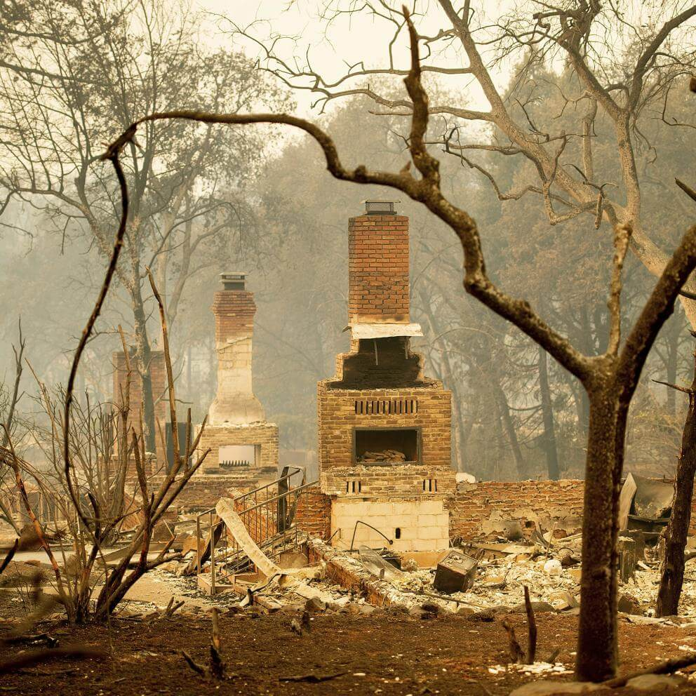 Brick fireplaces stand amid smoldering wreckage in Paradise, California, after fire destroyed the town November 8–9, 2018.