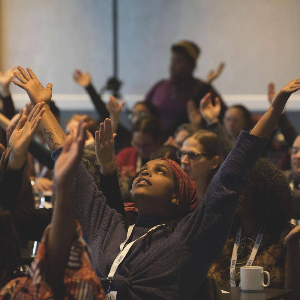 People raise their arms during a time of spiritual grounding at the BLUU Harper-Jones Theological Symposium on November 1