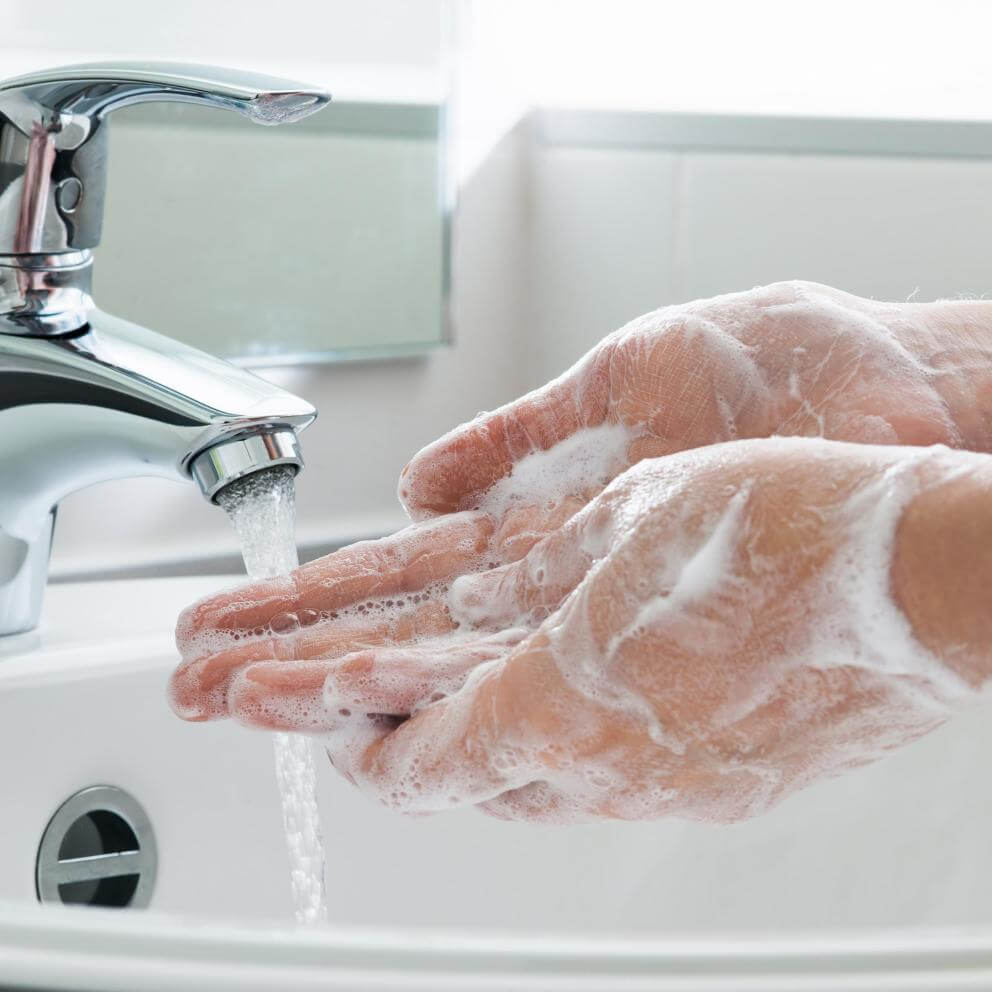 Closeup of a person washing their hands with soap and water