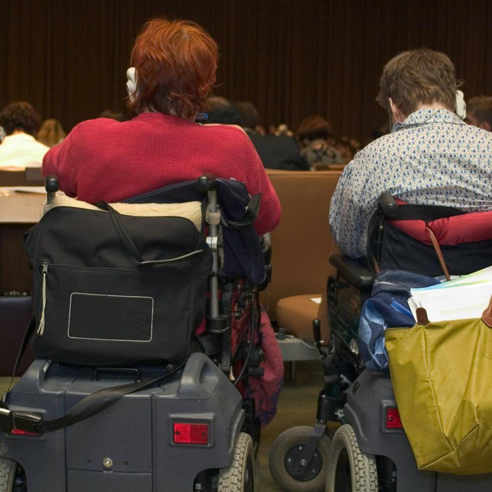photograph of 2 people in accessibility scooters, in the audience at a conference