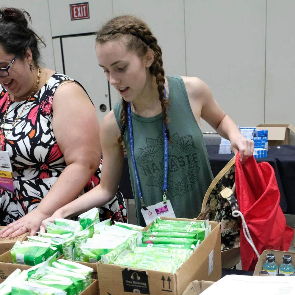 Audra Friend, UUA Communications Coordinator for Multicultural Ministries, and Marie Bennett, a youth from Davies Memorial UU Church in Camp Springs, Maryland, fill purses and bags with self-care items.