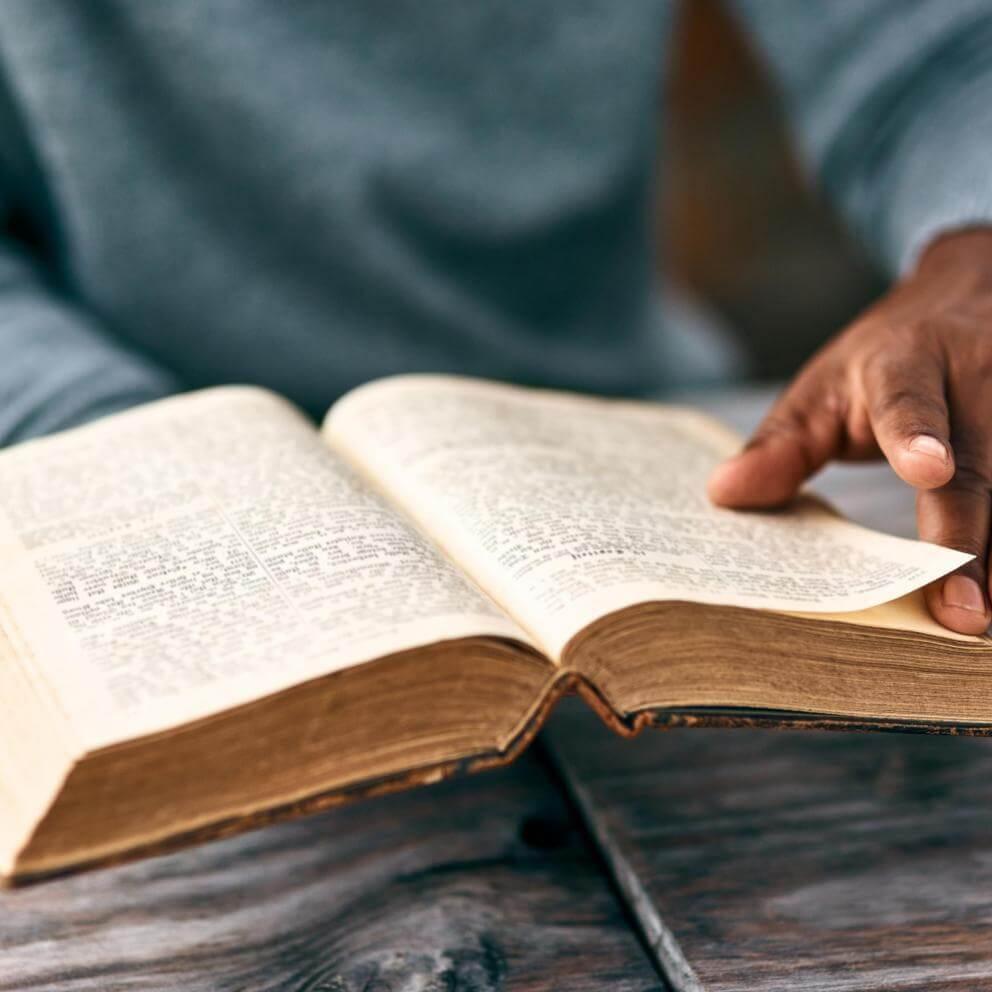 Stock photo of brown hands turning pages of an old book that looks like the bible.