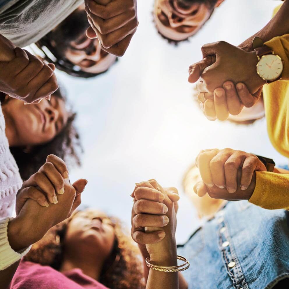 Stock photo of a group of black folx holding hands praying in a circle, photo taken from below.