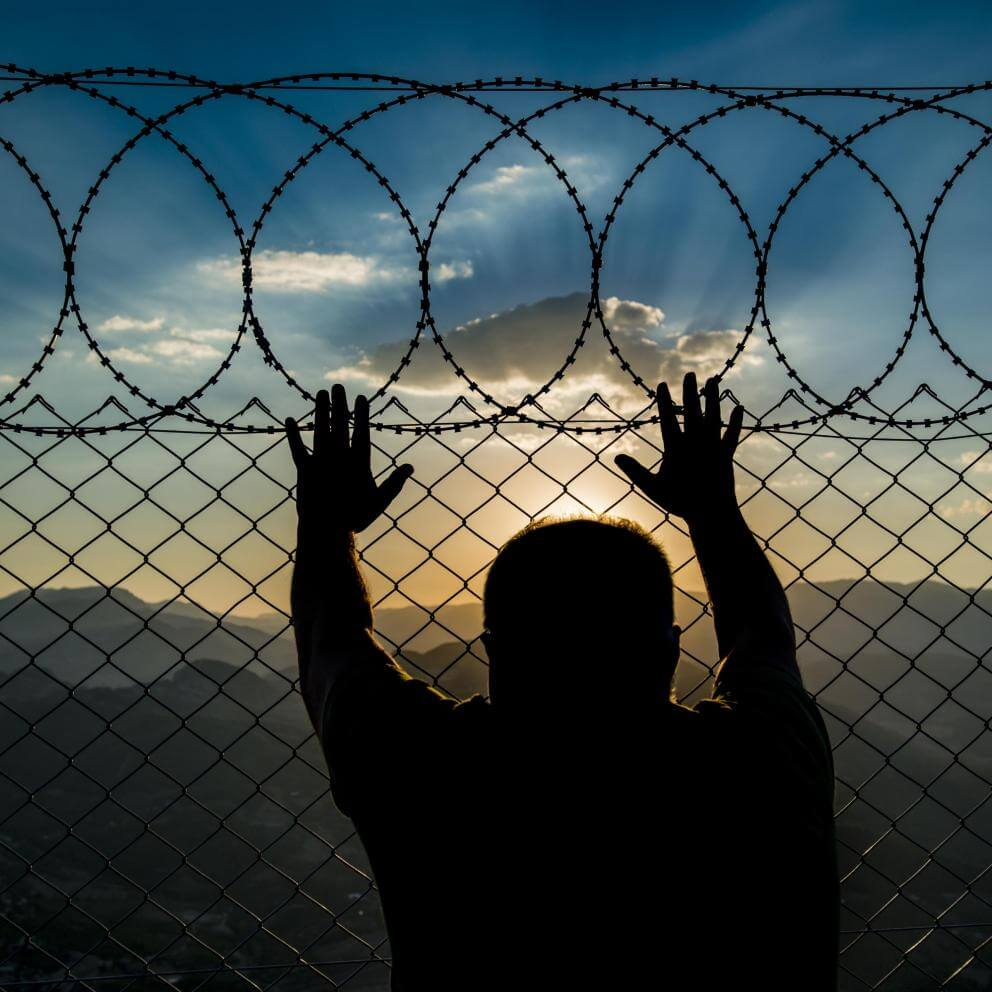 Stock photo of silhouette of person leaning against a chainlink fence topped with razor wire, looking out.