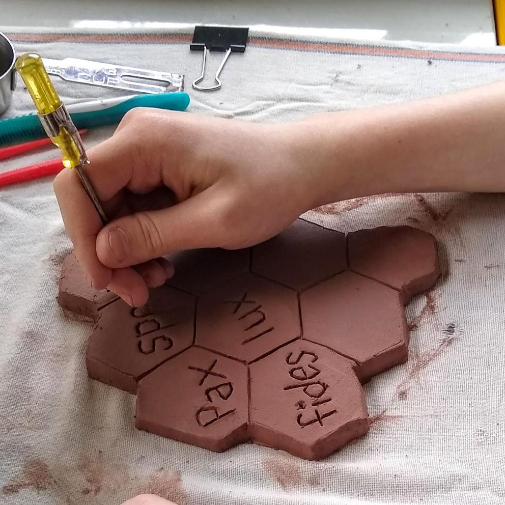 Rosalie Alff carves Latin words into clay that will become a chalice.
