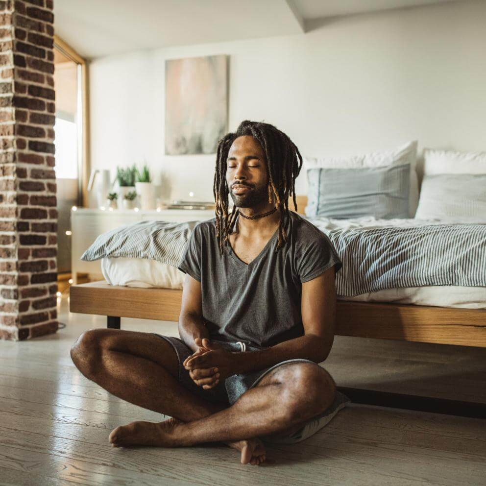 Stock photo of a young man practicing yoga at home. He is in bedroom and doing yoga, first thing in the morning.